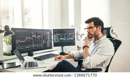 Trading online. Successful and young bearded trader in eyeglasses and formal wear working with laptop while sitting in his office in front of computer screens with trading charts #1388871770