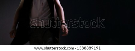Blurred in motion. A man walks in a T-shirt with blood drops. Feelings of fear. Abstract dark background for banner or invitation to a horror party. Halloween theme or maniac killers. #1388889191