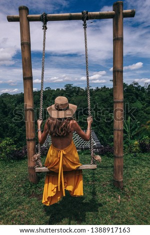 travel series. Fashion photo of beautiful woman with dark hair in yellow dress posing on the swing with Bali jungle view #1388917163