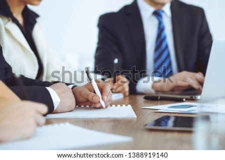 Group of business people or lawyers  work together at meeting in office, hands using tablet and making notes close-up. Negotiation and communication concept #1388919140