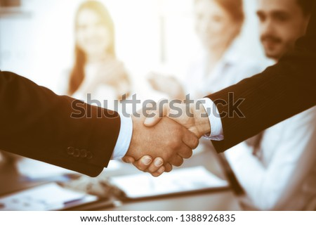 Business people shaking hands at meeting while theirs colleagues clapping and applauding. Group of unknown businessmen and women in modern white office. Success teamwork, partnership and handshake #1388926835