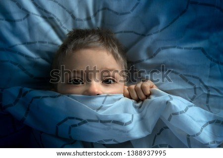boy in bed with his eyes open. the child is afraid of the dark. tormented by nightmares and terrible dreams in children #1388937995