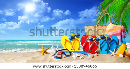 Tropical beach with sunbathing accessories, summer holiday background. Travel and beach family vacation #1388946866
