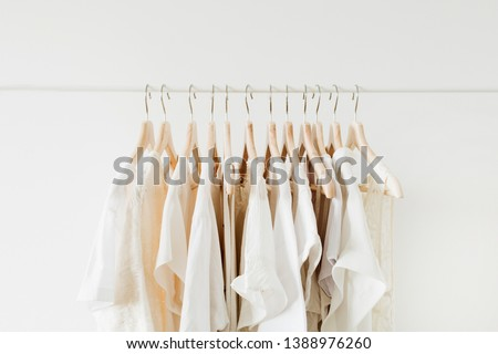 Minimal fashion clothes concept. White female blouses and t-shirts on hanger on white background. #1388976260