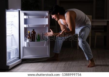 Man breaking diet at night near fridge #1388999756