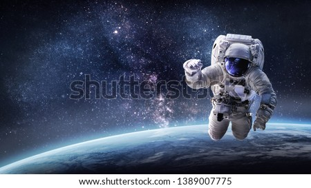 Astronaut in outer space over the planet Earth. Our home. ISS. Elements of this image furnished by NASA #1389007775