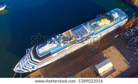 Vladivostok, Primorsky Krai - April 4, 2019: Vladivostok, Primorsky Krai - April 4, 2019: Aerial view of the cityscape with a white cruise liner in the port. #1389022016