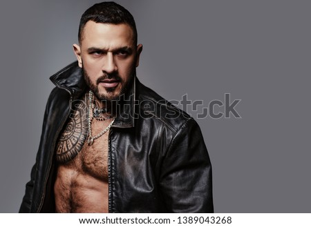 In his brutal style. Brutal hispanic man. Bearded latino man with brutal tattoo on muscular chest. Brutal and athletic, copy space. #1389043268