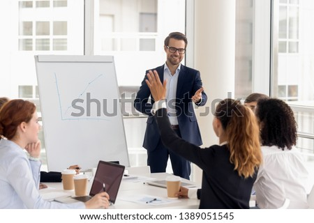 Smiling millennial male coach or presenter make flip chart presentation ask question during work training, motivated confident female employee raise hand answer engaged in teamwork at seminar Royalty-Free Stock Photo #1389051545