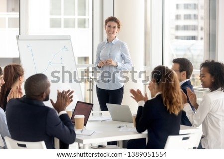 Multiethnic happy employees applaud thanking female speaker for successful flip chart presentation, excited diverse work group clap hands show gratitude to smiling woman coach seminar or training #1389051554