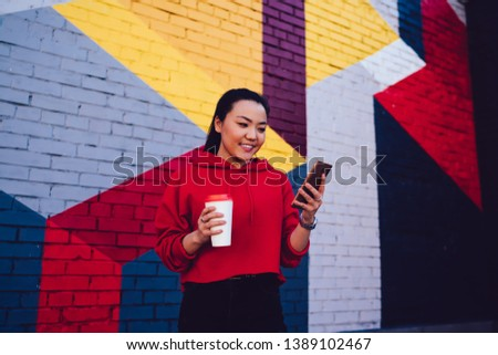 Cheerful asian woman dressed in casual wear enjoying time for reading funny publications on web page connected to public internet on cellular phone, positive hipster girl holding mobile gadget #1389102467