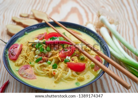 Close up picture of Soto ayam, spicy indonesian or malaysian soup consist from chicken meat, rice noodles, curry spice, spring onion,tomatoes and coconut milk served in bowl on the wooden table.