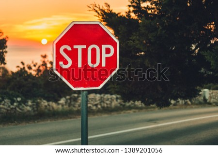 A traffic sign Stop in coastline with road  and sea on background - photo on sunset. Illuminated sign by the side of the road with trees and stone wall on background. Warm toned photo of Traffic sign.