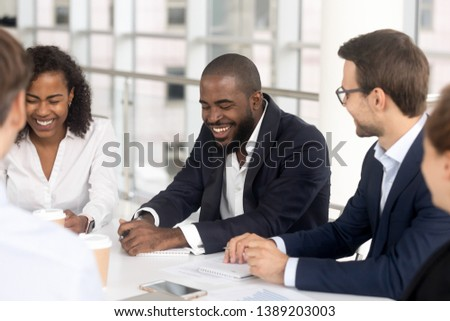 Smiling multiethnic millennial employees sit at office desk talk laugh at company boardroom meeting, happy diverse workers feel overjoyed brainstorm have fun joke at team meeting in conference room #1389203003