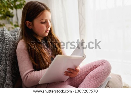 Cute little girl reading a book, at home by the window. Early reading. #1389209570