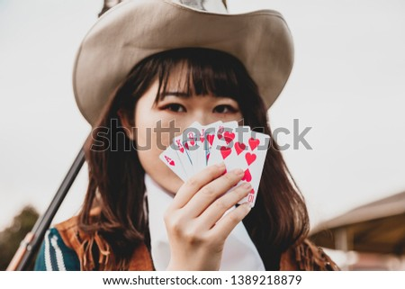 Portrait of a beautiful Chinese female cowgirl while playing with poker cards sitting outdoors