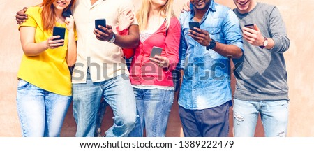 Teenagers texting mobile phone messages row on pink background - Multiracial friends holding smartphone smiling - Multicultural teens generation using cellphone - Modern communication concept - Image #1389222479