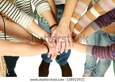 friends putting their hands together in a sign of unity and teamwork #138923921