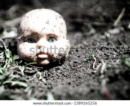 Old broken scary doll head on a ground in abandoned village. #1389265256