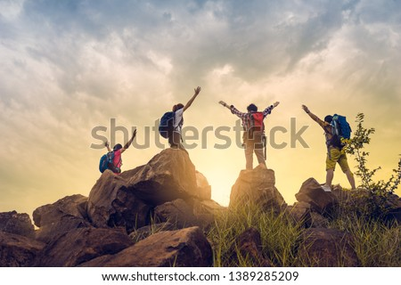 Adventure to overcome the limits of life, male and female hikers climbing up mountain cliff under sunrise. they are success full at top the mountain. helps and team work concept.  Royalty-Free Stock Photo #1389285209