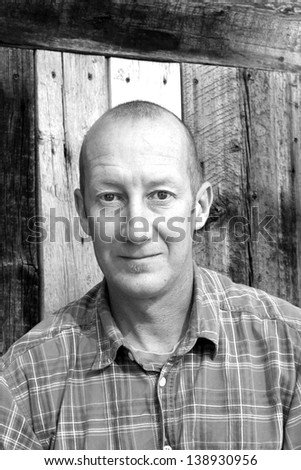 Black and white portrait of a man with a reclaimed wood background. Royalty-Free Stock Photo #138930956