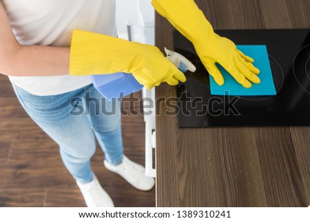 A young woman from a professional cleaning company cleans up at home. A man washes the kitchen in yellow gloves with cleaning supplies stuff. #1389310241