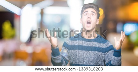 Young handsome man over isolated background crazy and mad shouting and yelling with aggressive expression and arms raised. Frustration concept. #1389318203