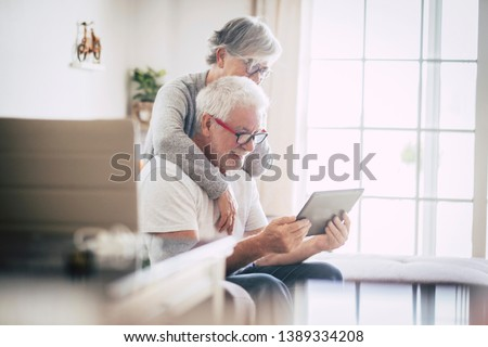 couple of seniors smiling and looking at the same tablet hugged on the sofa - indoor, at home concept - caucasians mature and retired man and woman using technology - lockdown and quarantine lifestyle Royalty-Free Stock Photo #1389334208