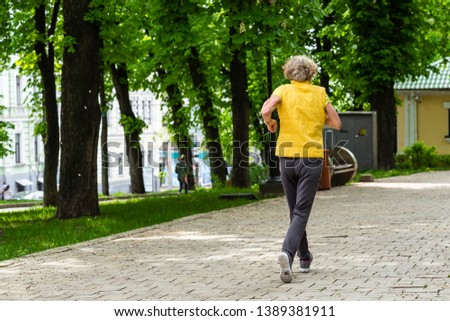 healthy lifestyle in the early morning in the morning a person plays sports runs on park paths #1389381911