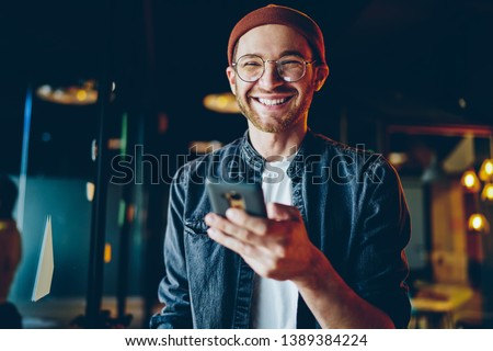 Funny caucasian male in casual wear laughing at content from social networks using mobile phone, positive millennial generation hipster guy satisfied with tariffs for 4G internet on smartphone #1389384224