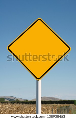 Blank yellow diamond road sign in a rural setting for use with your own text