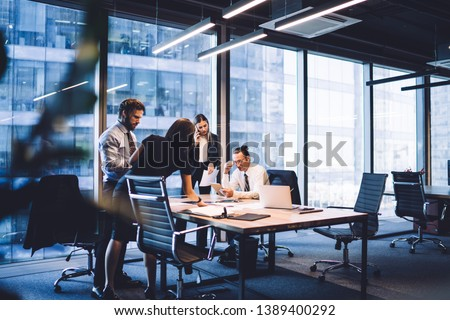 Cooperation process of professional male and female colleagues,business woman in formal suit communicate with operator via smartphone gadget while reading email from partners touch pad during teamwork Royalty-Free Stock Photo #1389400292