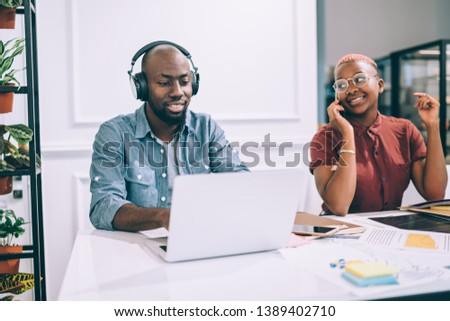 Cheerful African American female talking on phone and looking at male colleague using laptop and listening to music while working in cafe together #1389402710