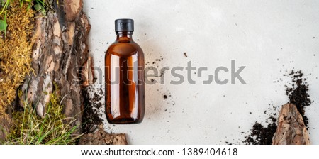 Environmentally clear nature concept background. Composition with glass bottle of shampoo over bark tree, moss and earth with grass for organic cosmetic products on white with copy space. #1389404618