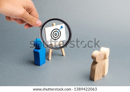 Magnifying glass is looking at leader explains employee tactics of advertising targeting. Training, briefing. Search strategies for effective advertising campaigns, customer reach. Business processes #1389422063