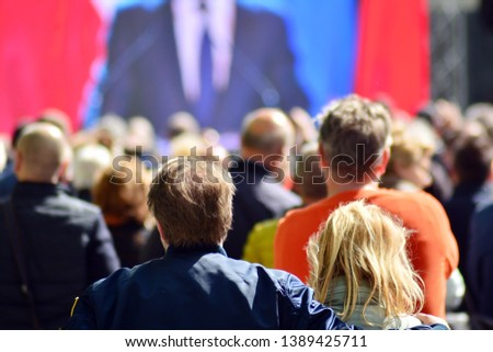 Crowd attending political meeting. Large group of   people as audience to politician's speech outdoors in big screen. #1389425711
