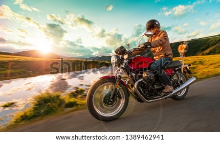 Motorcycle driver riding in Alpine highway, Nockalmstrasse, Austria, central Europe. #1389462941