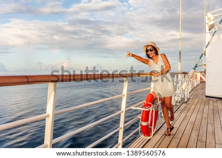 Happy cruise vacation fun travel woman pointing watching whales or wildlife sighting from deck of boat on Europe summer destination cruising vacation holiday. Luxury relaxation getaway.