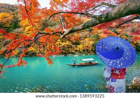 Asian woman wearing japanese traditional kimono at Arashiyama in autumn season along the river in Kyoto, Japan. #1389593225