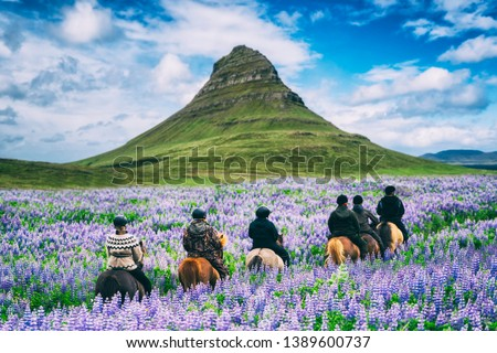 Tourist ride horse at Kirkjufell mountain landscape and waterfall in Iceland summer. Kirjufell is the beautiful landmark and the most photographed destination which attracts people to visit Iceland. #1389600737