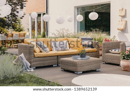 Real photo of a rattan garden furniture set with lamps and table in the background Royalty-Free Stock Photo #1389652139