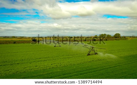 Irrigation system in a green field.  #1389714494