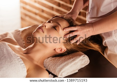 Hands of the masseuse make a manual massage of the head to a beautiful client woman. Concept of scalp treatment and hair growth stimulation #1389715193