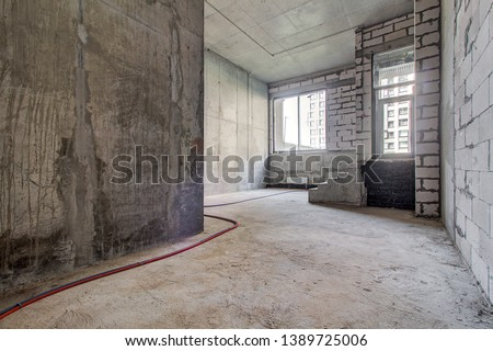 unfinished staircase to basement. Stairs architecture unfinished at basement. Cement concrete staircase on construction site. Empty and Bare Building Interior with Materials and Structure Exposed #1389725006