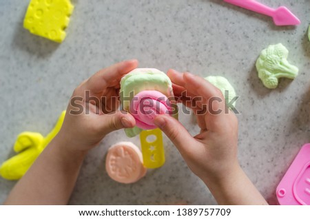 Child's hands with colorful clay. ice cream, fruits and vegetables from plasticine. Pastel color plasticine. Homemade clay. Close up