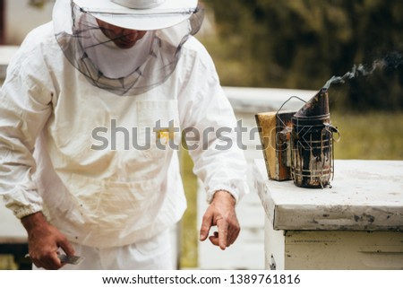 closeup of bee smoker on hive. man in background #1389761816