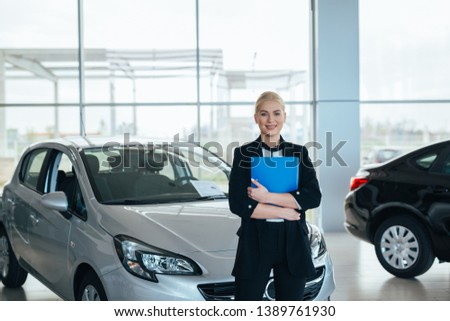 young saleswoman in car showroom standing crossed arms holding brochure #1389761930