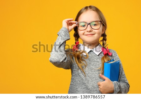 Portrait of a cute little kid girl on a yellow background. Child schoolgirl looking at the camera, holding a book and straightens glasses. The concept of education. Copy space. Royalty-Free Stock Photo #1389786557