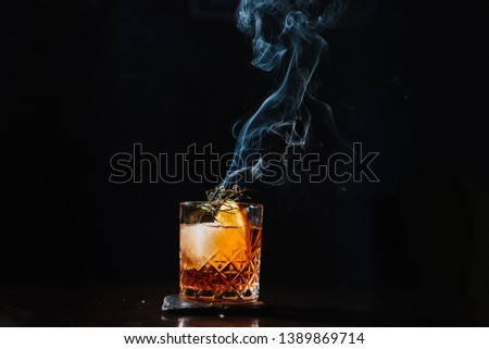 Whisky & Smoke. Smoking whiskey with ice and orange on a dark background. Cognac with smoking branch of lavender. Experimental alcoholic cocktail in a glass with smoking rosemary. Royalty-Free Stock Photo #1389869714
