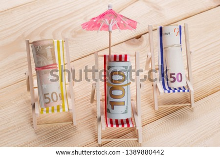 on the wooden flooring there are three chaise lounges, in the chaise lounges there are rolls of many dollar and euro bills, as if resting, the concept of travel and finance #1389880442